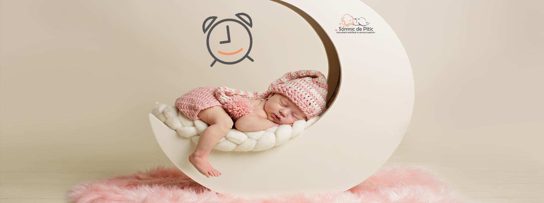 bebelus care doarme intr-un fotoliu semiluna