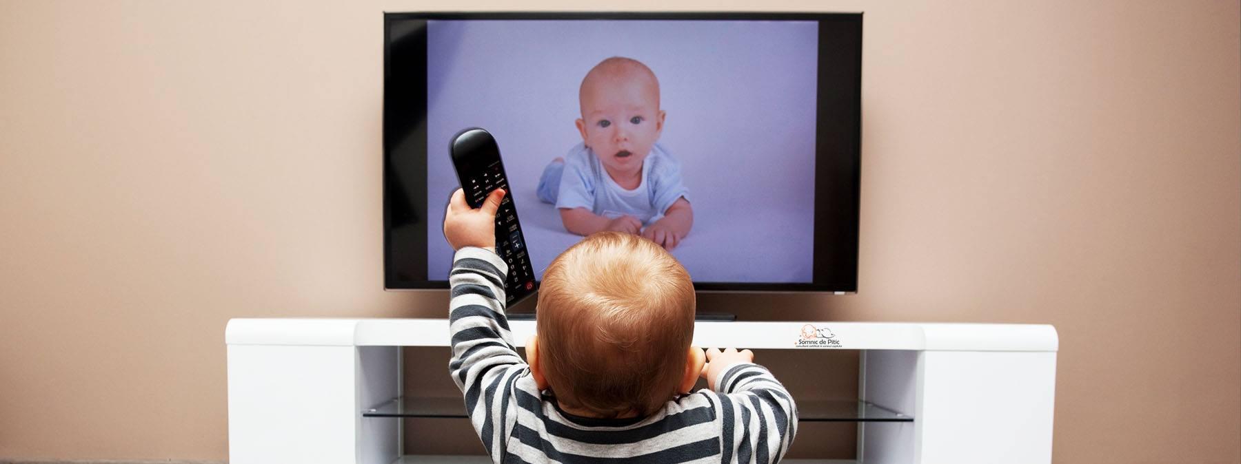 copil care se uita la un televizor cu bebelus pe ecran